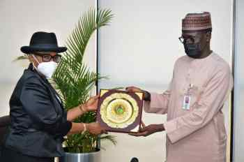 Group Managing Director of the Nigerian National Petroleum Corporation, Malam Mele Kyari (Right) presenting a plaque to the Pro Pro-Chancellor, Usmanu Danfodiyo University, Sokoto, Hon. Justice Pearl Enejere (rtd), during a meeting at the NNPC Towers, Abuja..
