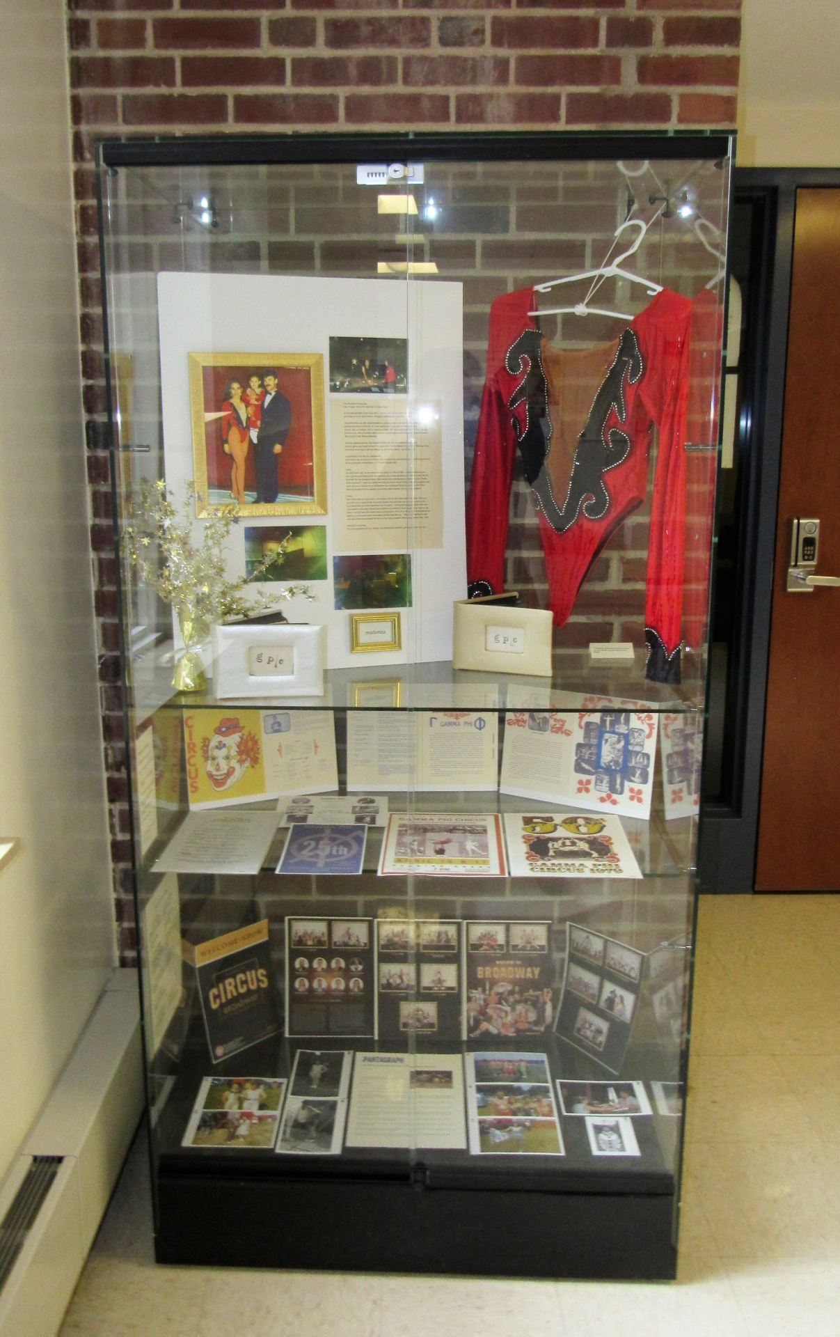 A photo of the glass case in the exhibit, which features the garment of a former Gamma Phi Circus member and other old relics such as photos and old programs of former circus performers.