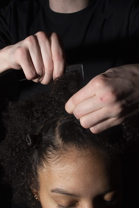 A photo of white hands combing the hair of a Black woman.