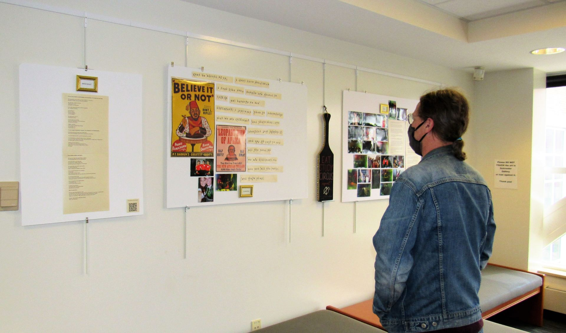 A visitor of the gallery viewing a decorated wall of the exhibit.