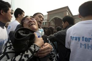 A relative of Chinese passengers on board a missing Malaysia Airlines plane breaks down as she protests