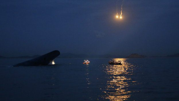 Flares light up the sky as the search for missing passengers continues through the night