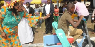 First Lady Nana Lordina Mahama assisting a boy to ride a tricycle at Children's hospital