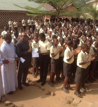 The Manager of St. Patrick Secondary School, Obollo-Eke , Rev. Fr. John Martins Chikan ( left) at the presentation by Mr. Peter Obi ( middle) of the cheque of N2 million Naira to the school represented by the Senior Prefect of the School, Master Aba Candidus ( right) amongst other students