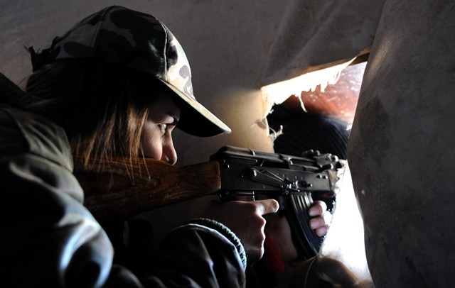 A female sniper takes positon in a buliding in Daraya suburb of the capital Damascus, Syria, on April 5, 2015. The snipers are members of the female force in Syrian Republican Guards. Their unit consists of around 800 volunteer, unmarried, female fighters- aged between 20 and 24 years old. Their task is to work alongside the Syrian army in its battle against the rebels. (Xinhua/Zhang Naijie) (jl)