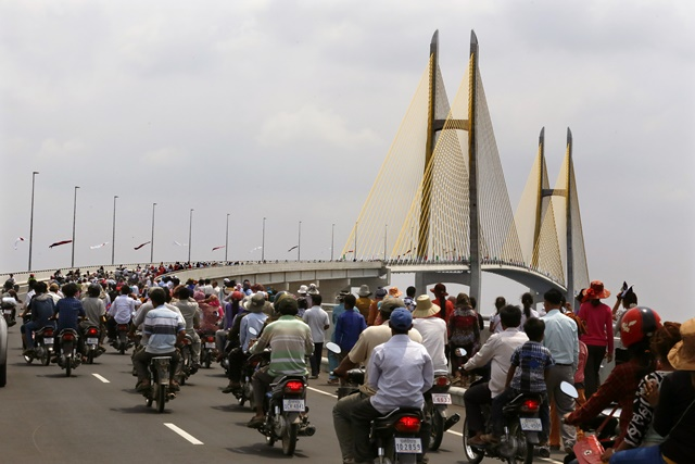 People travel on the newly-built Tsubasa Bridge, better known as Neak Loeung Bridge, in Kandal province, Cambodia, April 6, 2015. Cambodia on Monday inaugurated the 127-million-U.S. dollar Japanese-funded Tsubasa Bridge, linking southern Kandal and Prey Veng provinces, to boost trade and travel between Cambodia and Vietnam. (Xinhua/Phearum) (lrz)