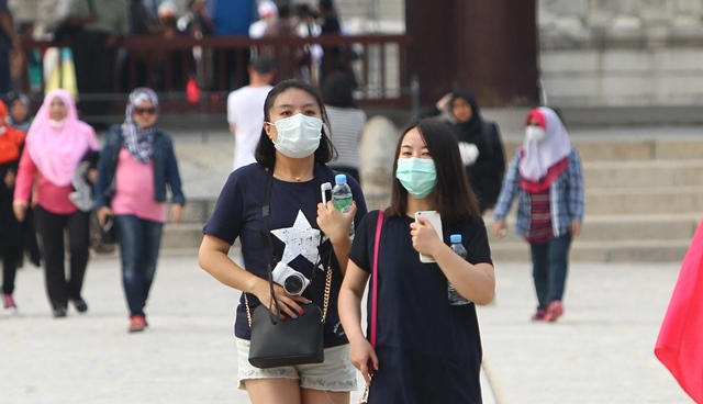 Tourists walk with masks at the Gyeongbokgung Palace in Seoul, South Korea, June 8, 2015. South Korea on Monday identified 23 new contagions with the Middle East Respiratory Syndrome (MERS), increasing the total number to 87 while deaths from the viral disease rose to six as one more death was reported. (Xinhua/Yao Qilin) (dzl)