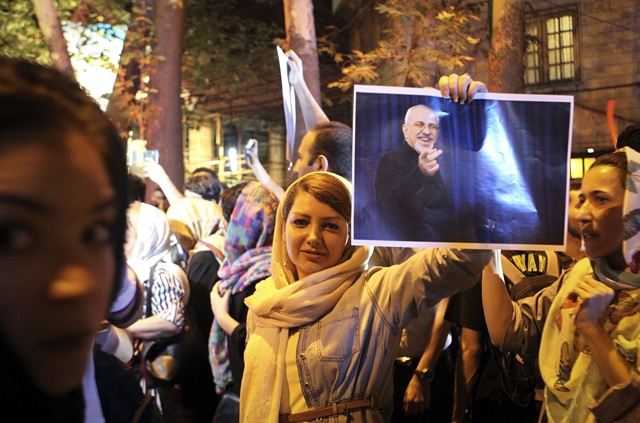 A woman holds a poster of Iranian Foreign Minister Mohammad-Javad Zarif to celebrate the nuclear agreement in Tehran, Iran on July 14, 2015. The nuclear deal between Iran and the world powers will open a new chapter in the relations between Iran and the International community, Iran's President Hassan Rouhani said Tuesday. (Xinhua/Ahmad Halabisaz)