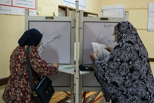 Voters write their ballots at a polling station in Cairo, Egypt, on Nov. 22, 2015. Egyptians began voting Sunday in the second phase of the country's first parliamentary election since Islamist President Mohamed Morsi was ousted in 2013. (Xinhua/Pan Chaoyue)