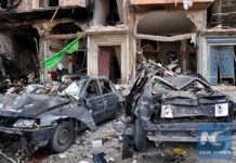 A picture taken on February 21, 2016 shows damaged cars at the site of a double car bomb attack in the Al-Zahraa neighborhood of the central Syrian city of Homs. (AFP photo)