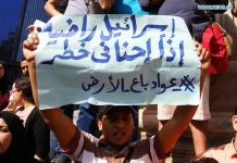 AIRO, April 15, 2016 (Xinhua) -- A protestor holds a placard during a demonstration protesting against the Egyptian government's decision to transfer two Red Sea islands to Saudi Arabia in front of the Journalists Syndicate in Cairo, Egypt on April 15, 2016. Hundreds of Egyptians gathered Friday afternoon outside the press syndicate in Cairo to protest against Egypt's recent official transfer of two controversial islands to Saudi Arabia. (Xinhua/Ahmed Gomaa)