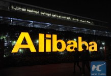 Two staff members walk past the logo of Alibaba at Alibaba Group's Xixi base in Hangzhou, capital of east China's Zhejiang Province on Nov. 12, 2014. [Photo/Xinhua]