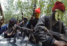 Okrika, NIGERIA: Masked Ateke Tom militants hold their guns as they arrive at their camp, 13 April 2007, in Okrika, Rivers State. Ateke Tom is the leader of the Niger Delta Vigilante, an ethnic Ijaw militia in the Niger Delta region of Nigeria. Many militant groups in the delta say they are fighting for the control of government oil wells. Five people, including a senior police officer, were killed in clashes between rival cult gangs in southern Nigeria's oil-rich state of Rivers, the police said today. AFP PHOTO / LIONEL HEALING (Photo credit should read LIONEL HEALING/AFP/Getty Images)