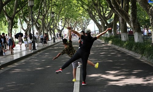 Two tourists in Hangzhou, East China's Zhejiang Province - which will host the G20 summit in September - pose for a photo on the empty street around West Lake on Thursday. As the summit approaches, traffic control measures have reduced the number of cars running on several streets around the lake. Photo: IC