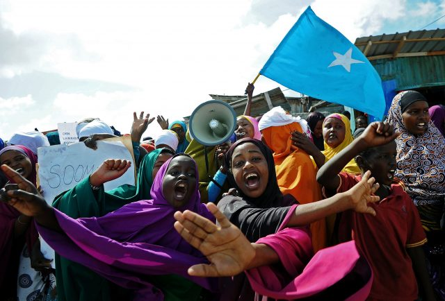 Demonstrators hold placards during a protest against Al shabab insurgents outside Lido beach in the Somali capital Mogadishu, on January 28, 2016. Al Shebab killed at least 19 people when five gunmen detonated a bomb before storming a restaurant in the at Lido beach on January 22, 2016. / AFP / MOHAMED ABDIWAHAB