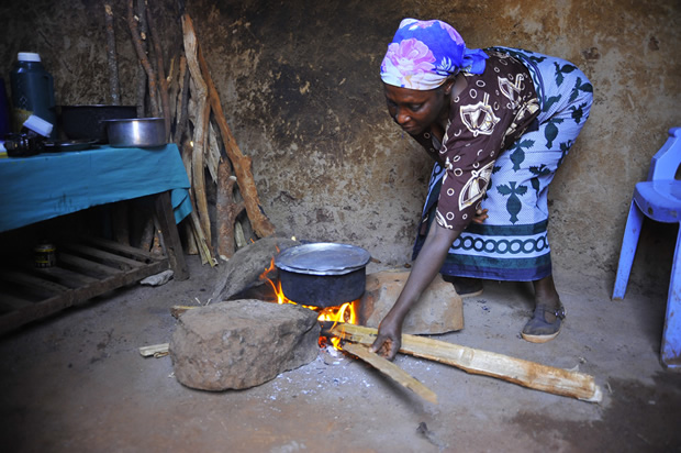 This young woman has to continuously feed her cooking fire with wood, which burns less efficiently than it would in an improved cookstove. Photo credit: Alex Kamweru/UN Foundation