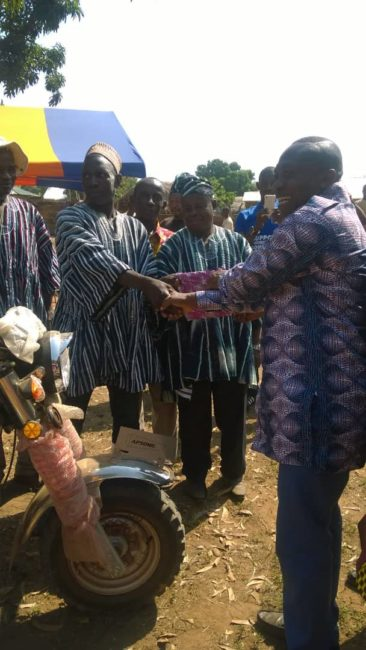 The MCE, Hon. Michael Sarkodie (right) handing over the tri-cycle to Thomas Mankire (left)