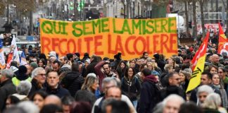 """People hold a banner reading """"who sows misery reap the rage"""" as they take part in a demonstration to protest against the pension overhauls, in Marseille, southern France, on December 5, 2019 as part of a national general strike. - Trains cancelled, schools closed: France scrambled to make contingency plans on for a huge strike against pension overhauls that poses one of the biggest challenges yet to French President's sweeping reform drive. (Photo by CLEMENT MAHOUDEAU / AFP)"""