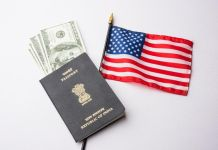 Indian passport with US currency notes and American flag in the background, symbolizing the effort of Indian workers seeking American H-1B visas to immigrate to America and earn American currency. Indian and Chinese workers are the ones most involved in the H1B visa program and affected by delays related to transitioning to green cards. GETTY