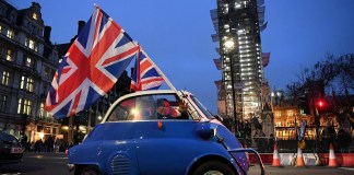 A man waves Union flags from a small car as he drives past Brexit supporters gathering in Parliament Square, near the Houses of Parliament in central London on January 31, 2020 on the day that the UK formally leaves the European Union. - Britain on January 31 ends almost half a century of integration with its closest neighbours and leaves the European Union, starting a new -- but still uncertain -- chapter in its long history. (Photo by DANIEL LEAL-OLIVAS / AFP)