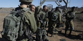 """Israeli soldiers gather on November 20, 2019 near the settlement Merom Golan in the Israeli-annexed Golan Heights, seized from Syrian in the 1967 Arab-Israeli war. - The Israeli army carried out a """"wide-scale"""" attack against Iranian forces and Syrian army targets in Syria early on November 20, killing at least 11 fighters, the Israeli army and a monitoring group said. In a rare confirmation of their operations in Syria, the Israeli army said they carried out dozens on strikes against the Iranian elite Quds Force and the Syrian military, in response to four rockets fired at Israel a day before. (Photo by JALAA MAREY / AFP)"""