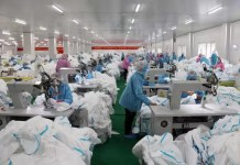 Photo taken on Feb. 8 shows workers busy with production of medical protective supplies in a workshop of a local company in Xiantao, central China's Hubei Province. (Hou Linliang/People's Daily)