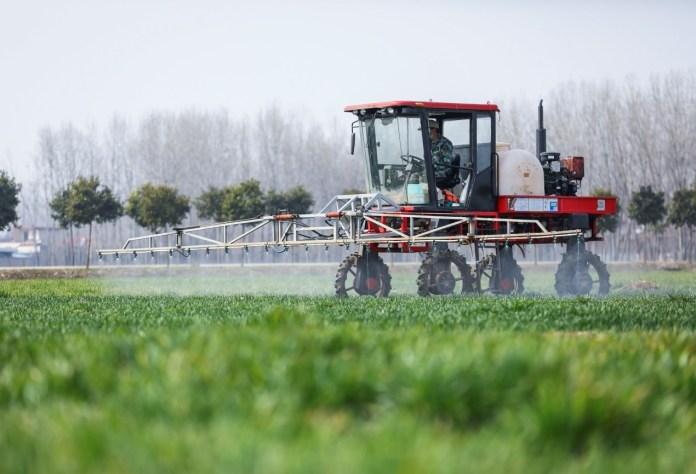 Farmer Kong Debin works in the field driving an agricultural sprayer in Donglonggang village, Jisuo township, Tengzhou, east China's Shandong province, Feb. 20, 2020. (Photo by Song Haicun/People's Daily Online)