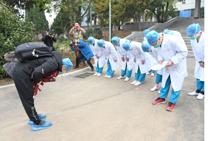 A cured novel coronavirus pneumonia patient bows to medical staff after being discharged from Huainan First People's Hospital, east China's Anhui province, March 6. He is one of the last three patients discharged from the hospital. Photo by Chen Bin, People's Daily Online