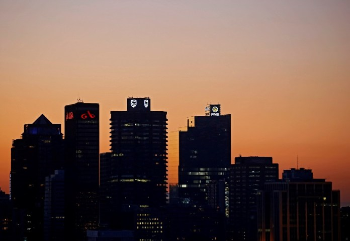 FILE PHOTO: The buildings with the logos of three of South Africa's biggest banks, ABSA, Standard Bank and First National Bank (FNB) are seen against the city skyline in Cape Town, South Africa, September 3, 2017.REUTERS/Mike Hutchings/File Photo