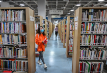 A woman searches for books in Chongqing Library, a public library in southwest China's Chongqing municipality. While making continuous efforts to prevent and control COVID-19, the library sees an increasing number of readers since it reopened in late March. (Photo by Wan Nan/People's Daily Online)