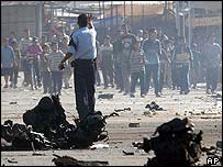 An Iraqi policeman tells people to stay away from the blast scene