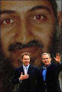 UK Prime Minister and US President George W Bush stand behind a picture of Osama Bin Laden