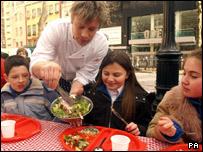 Jamie Oliver serving some children