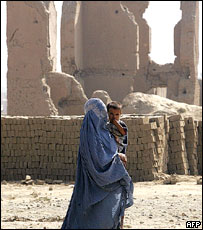 Woman and child pass by ruined buildings in Kabul