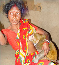 India woman suckling pet monkey