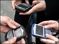 Three people using Blackberry mobile device