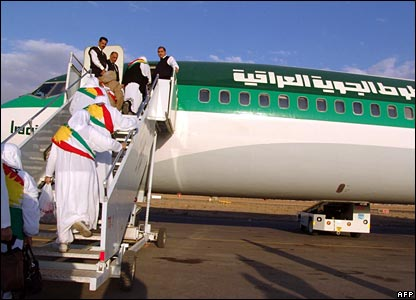 Kurdish Iraqi women, draped with the Kurdish flag, get onto an Iraqi airways plane heading Saudi Arabia