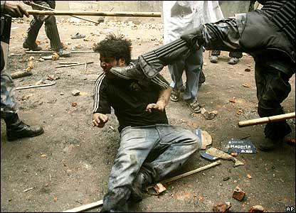 Policeman kicking demonstrator