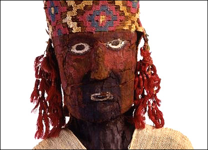 Figura tallada en madera con detalle de cruz andina en el sombrero.