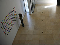 A woman examines Damien Hirst's spot painting