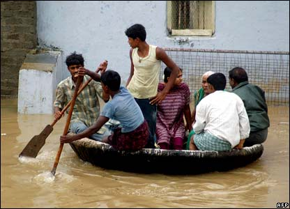 Indian villagers move through floodwaters in a local boat at Allampur village in Kurnool district.