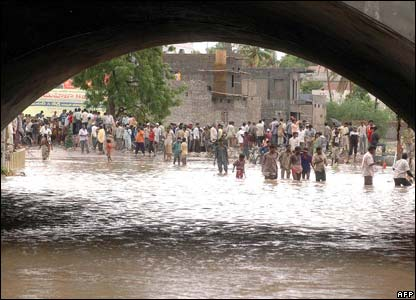 People gather on the banks of the swollen Handri river in the Kurnool district.