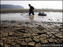 Un pescador chino buscando peces en el lago desecado de Dongting en enero de 2007