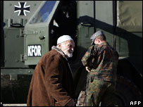 Kosovo Albanian man passes German Kfor peacekeeper, Prizren, 2007