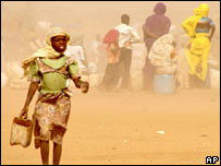 Girl in Darfur carrying water in a sandstorm