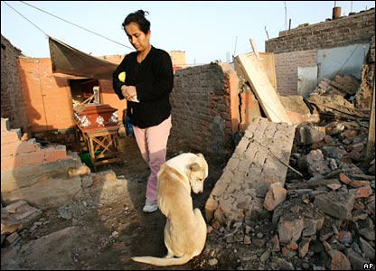 In the rubble of a home, a woman stands by the coffin of her uncle in Peru.