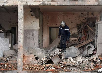 A firefighter searches the rubble of a destroyed building near the UN offices
