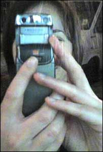 Woman taking photo with mobile phone, BBC