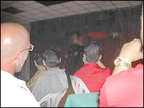 People watch a show by a drag queen at a Cuban night club (identity obscured)