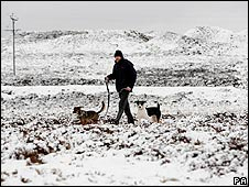 A man walking dogs in snow in Co Durham on 5th April